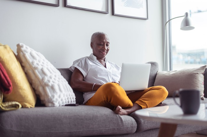 Smiling senior sitting cross-legged on couch looking at laptop.
