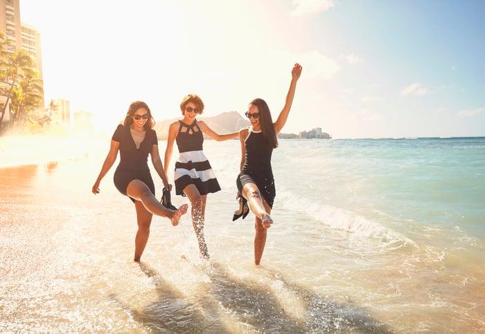 Three friends wearing dresses and splashing water on the beach.