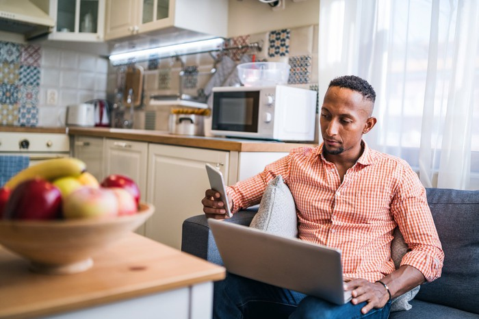 Person in home with laptop and smartphone.