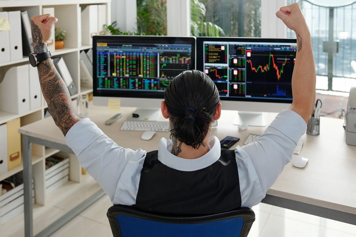 A person raising his hands in celebration while looking at stock price charts on a computer screen.