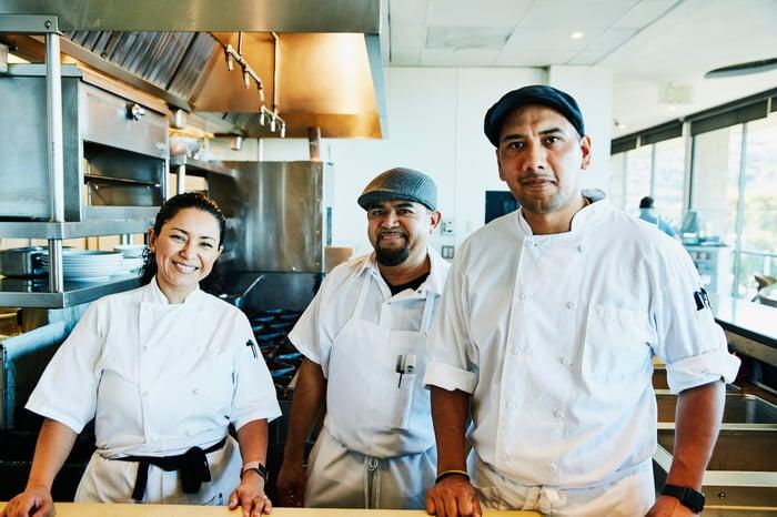 Three chefs standing in the kitchen.