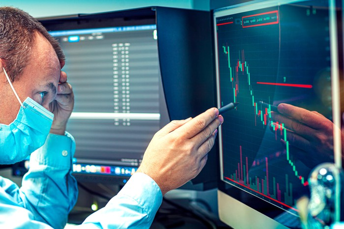 A worried business person in a protective mask studies a falling stock price chart on a computer screen.