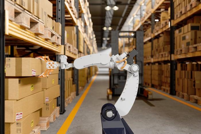 Robot in warehouse pulling box off shelf.