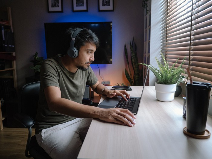 Young person wearing headphones navigates on a laptop while sitting at a desk.