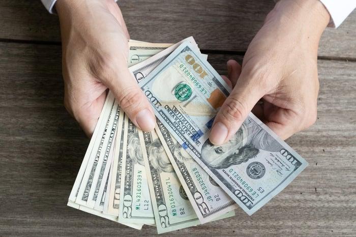 Une personne détenant un assortiment de billets de banque en éventail.