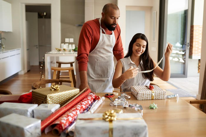 Two people wrapping presents in a home.