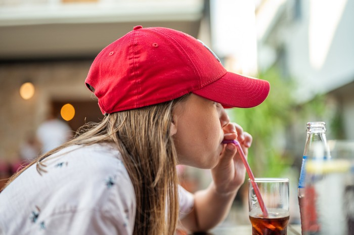 Person in red hat drinking from a glass of cola with a straw.