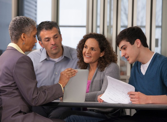 Four people sit at a table looking at paperwork.
