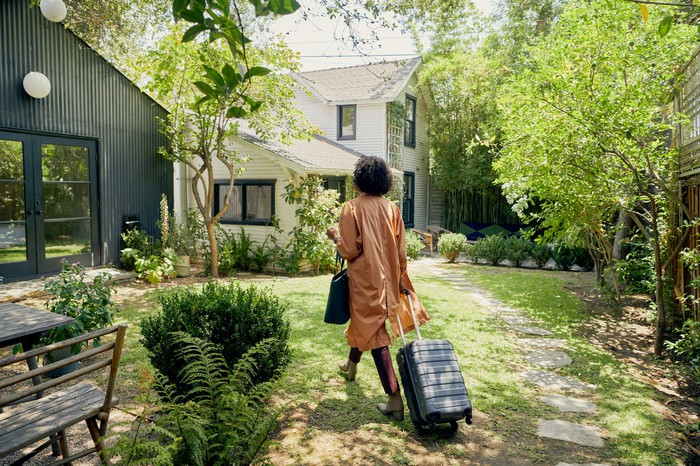 A person pulling a suitcase and walking up to an Airbnb residence.