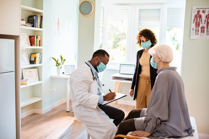 A doctor seeing an elderly patient in a checkup room while a third person observes.