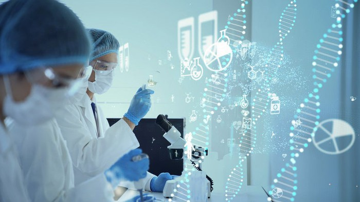 Scientists work in a lab with a graphic image of coded DNA in the background.
