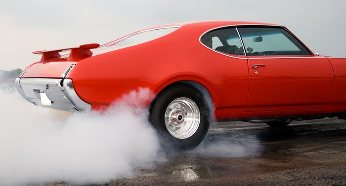 Red muscle car burning rubber