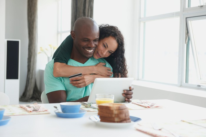A couple looking at a tablet during breakfast.
