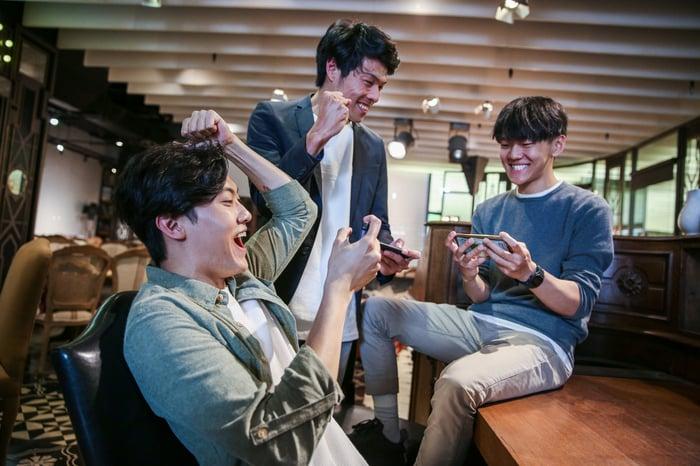 Trois personnes souriantes sur leurs smartphones.