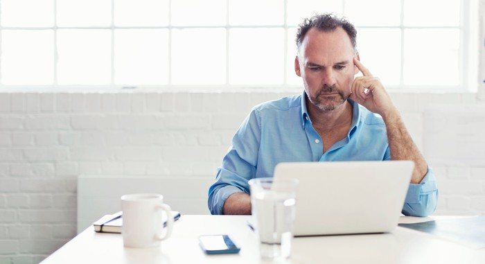 Person at laptop with serious expression