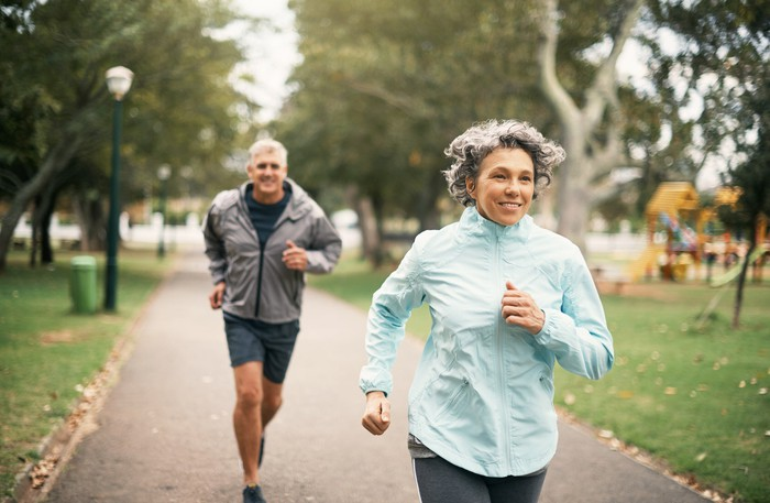 Two seniors running outdoors.