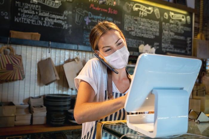 Barista processes a transaction at a coffee shop.