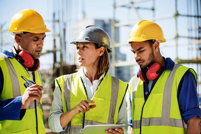 Three people looking at a mobile device on a construction site.