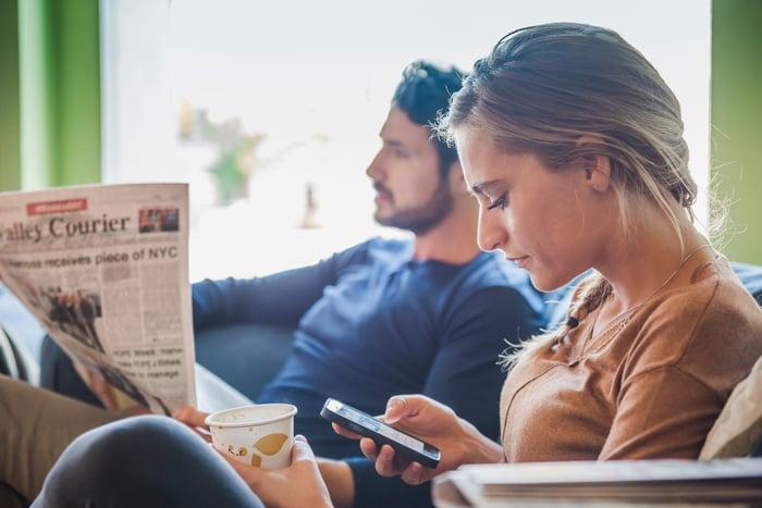 Deux personnes, dont l'une lit un journal, l'autre regarde un smartphone.