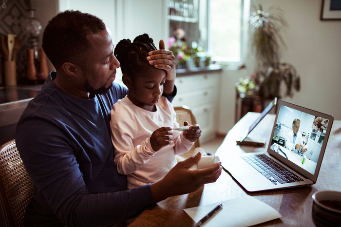Father and daughter engaging with a physician on the computer.