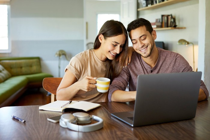 Two people smiling while looking at a laptop screen.