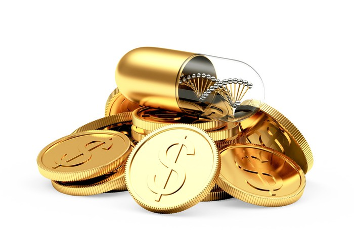 A gold capsule containing a DNA strand on top of gold coins with dollar signs on them.