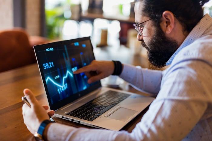 Un homme barbu est assis à une table en regardant un ordinateur portable et en montrant un tableau de fièvre à l'écran