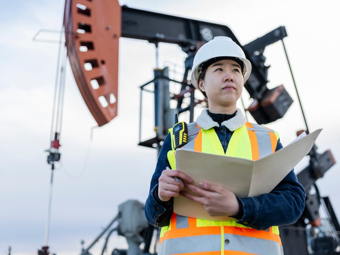 A person holding a folder in front of an oil pumpjack.