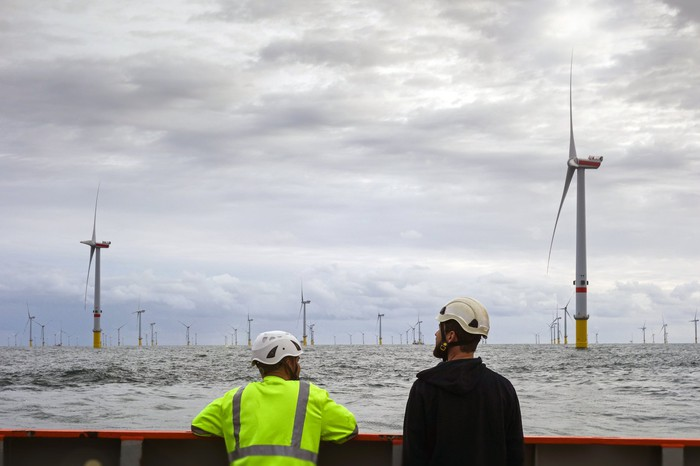 Two workers in hard hats look at an offshore wind energy farm from a vessel.