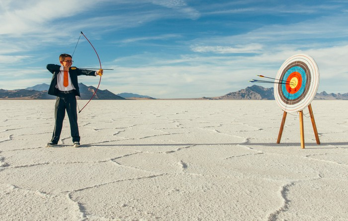 a young man in a business suit prepares to shoot an arrow from a bow at a nearby target while standing on white sands in a desert setting with mountains and blue skies in the background