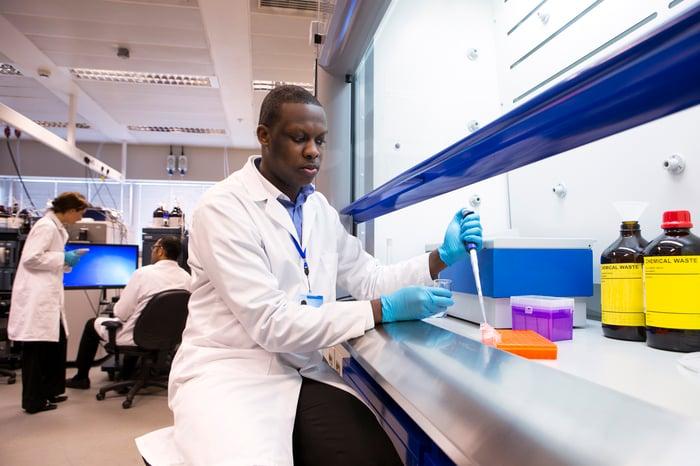Un technicien de laboratoire utilisant une pipette pour placer des échantillons liquides dans un plateau.