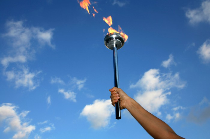 Person holding lit torch in the air.