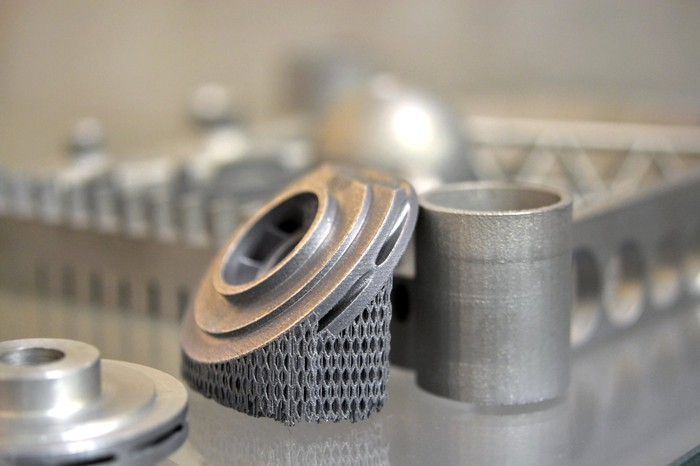 Several 3D-printed metal objects of different shapes and sizes.