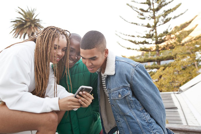 A trio of people look at one's smartphone outdoors.
