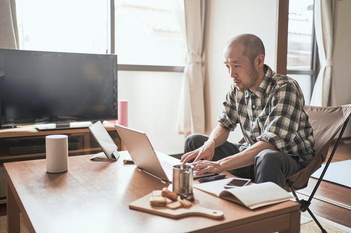 Une personne mûre travaille sur un ordinateur portable à la maison.