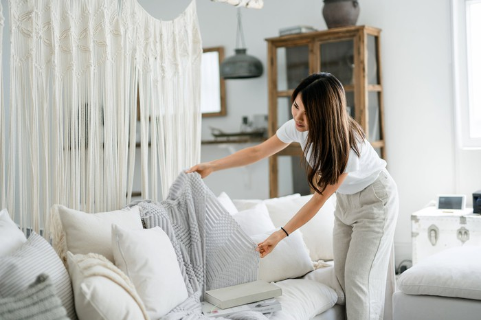 A home owner laying a matching blanket on a sofa in a living room.