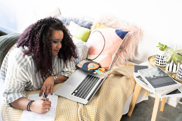 Person lying on bed looking at laptop screen and writing note.