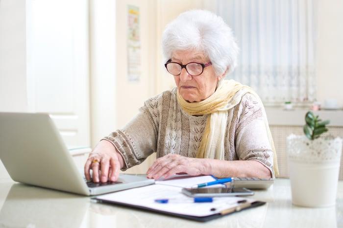 Concerned senior looking at laptop.