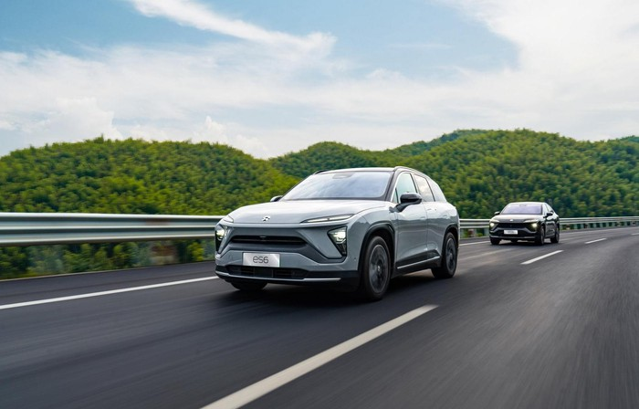 A NIO ES6, an upscale five-passenger electric SUV, is shown leading a NIO EC6 on a mountain road.