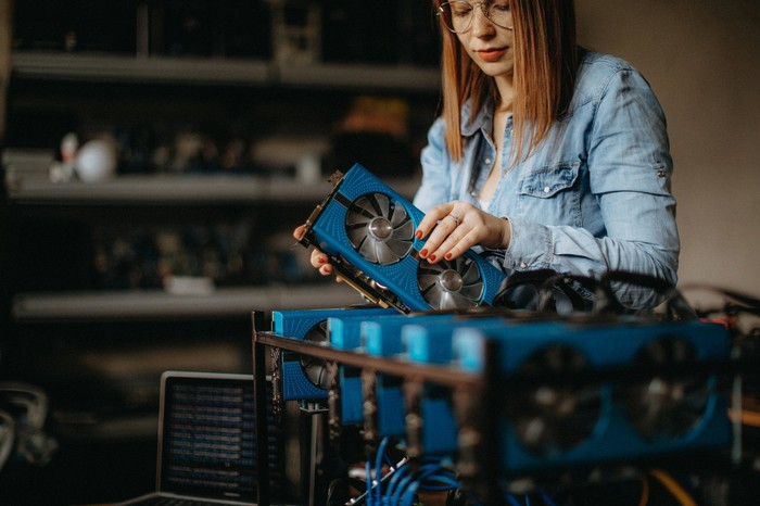 A young woman assembles a computer to mine Bitcoin.