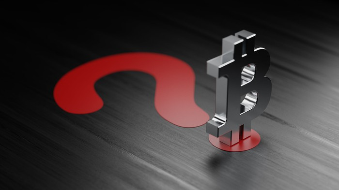 A Bitcoin symbol on top of a large, red question mark.