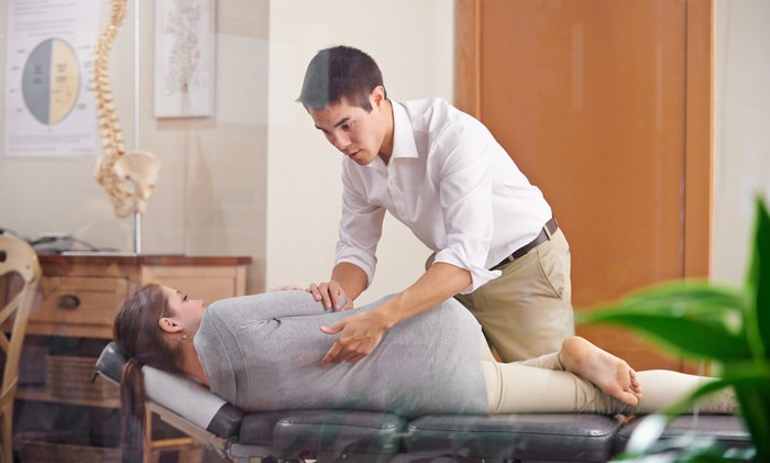 Chiropractor performing chiropractic adjustment on a patient.