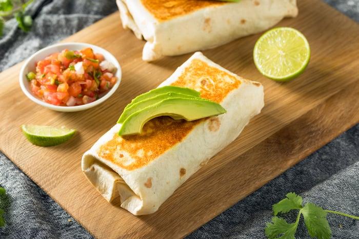 A burrito on a cutting board.