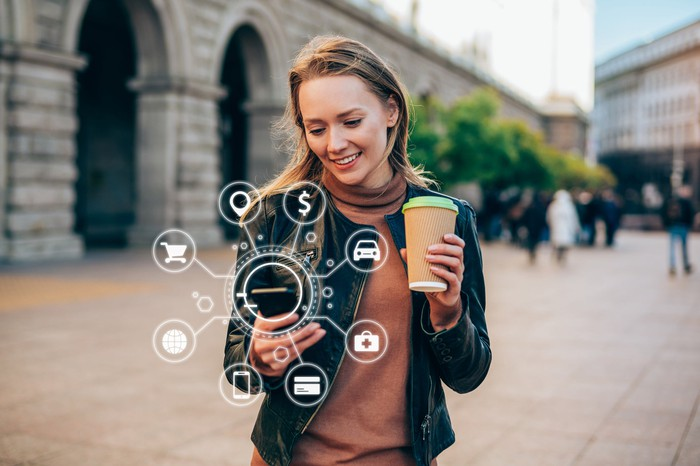 Woman using a mobile phone, overlaid with various digital icons (shopping, search payments, maps, etc.)
