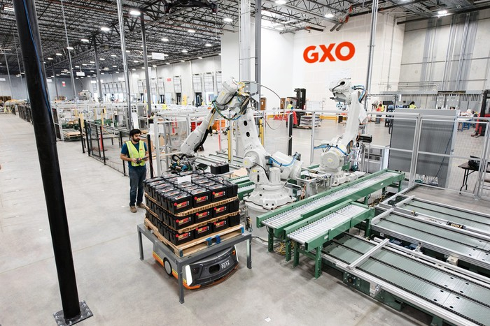 An employee operates a robotic arm at a GXO warehouse.