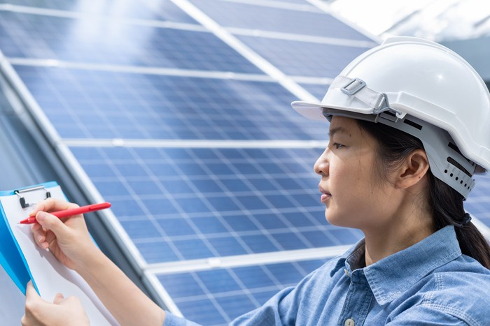 A worker writes on a clipboard while leaning against a solar panel.