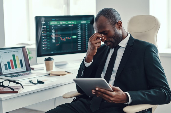 A frustrated investor is surrounded by screens showing down stock data.