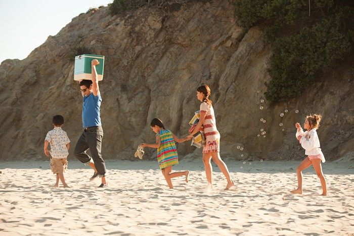An adult carrying a cooler while leading children to the beach.
