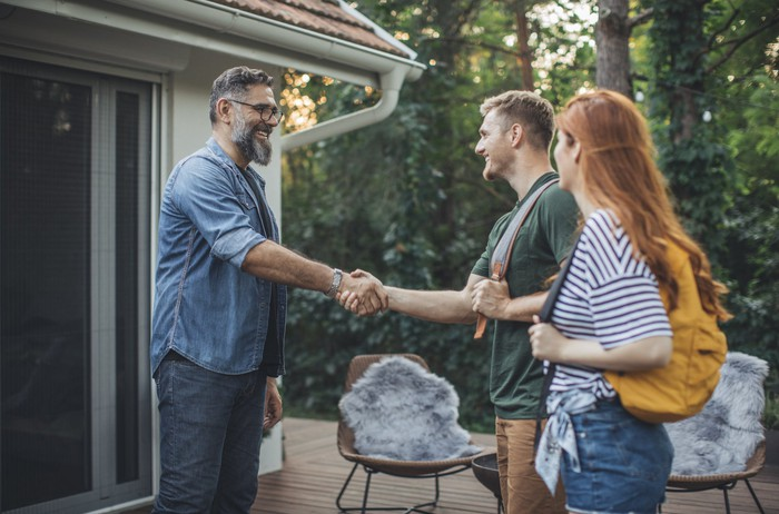 Three people meet on the deck of a home.