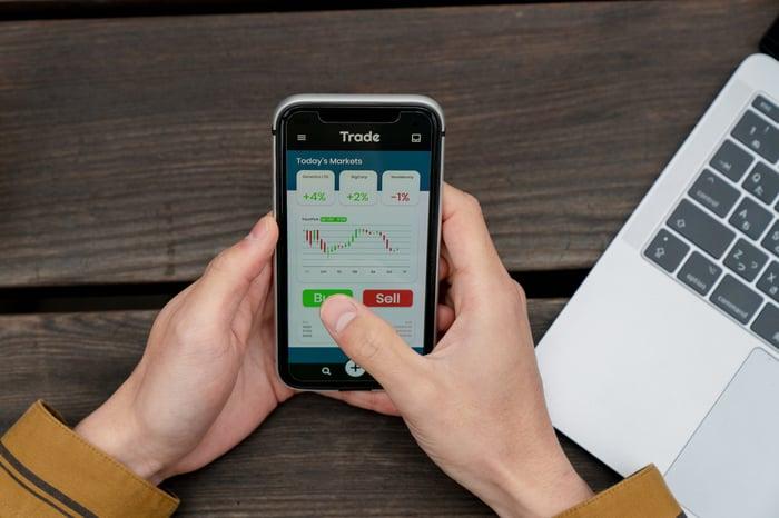 Personne utilisant un téléphone portable pour acheter des actions.